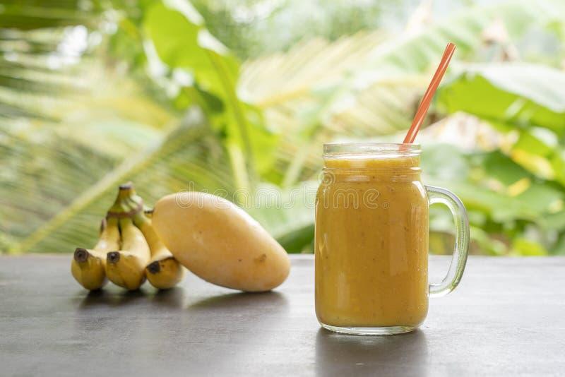 Smoothie с тропическими плодами: манго, банан, ананас в стеклянном опарнике на деревянном столе r стоковые фотографии rf