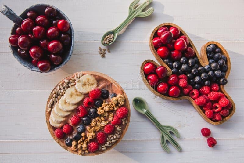Smoothie Acai, granola, семена, свежие фрукты в деревянном шаре с ложкой кактуса Плита заполненная с ягодами на белизне стоковая фотография rf
