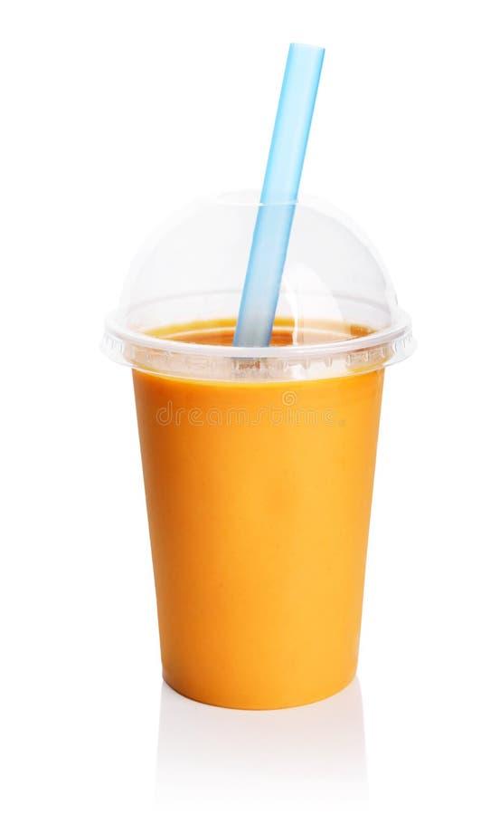 Smoothie anaranjado en taza transparente plástica foto de archivo libre de regalías