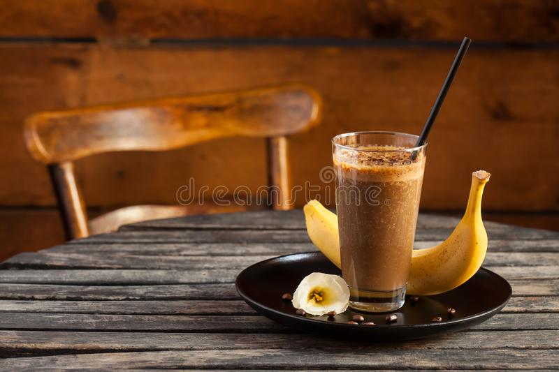 Smoothie with banana and coffee on rustic wooden table stock photography