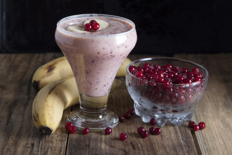 Smoothie of banana and frozen cranberries . Smoothie of banana and frozen cranberries with yogurt on an old table royalty free stock images