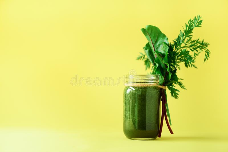 Smoothie with beet greens and carrot tops on yellow background, copy space. Summer vegan food concept. Healthy detox. Eating, alkaline diet. Fresh squeezed royalty free stock images