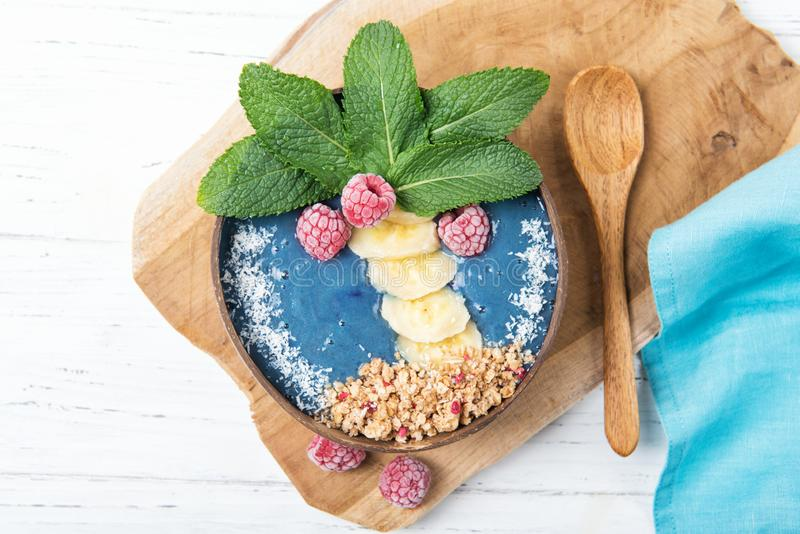 Smoothie bowl with blue spirulina and fresh fruits in a shape of palm tree, healthy breakfast idea, food for kids, top view royalty free stock image