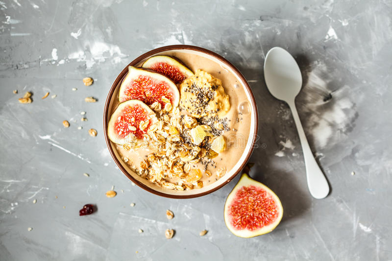 Smoothie bowl with figs, peanut butter and muesli. Love for a healthy vegan food concept stock photo