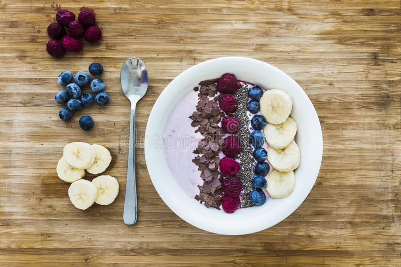 Smoothie bowl with fresh berries, banana, chia seeds and chocolate for healthy vegan and vegetarian diet breakfast royalty free stock images