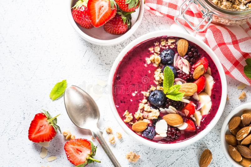Smoothie bowl from fresh berries, nuts and granola. Smoothie bowl with fresh berries, nuts and granola. Top view on white background. Healthy snack or breakfast stock photo