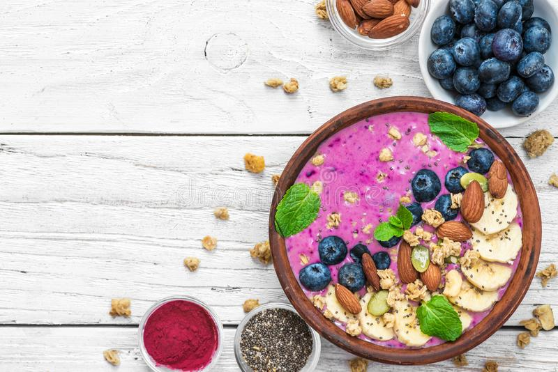 Smoothie bowl with fresh berries, nuts, seeds, granola and mint for healthy vegan diet breakfast on white wooden table stock images