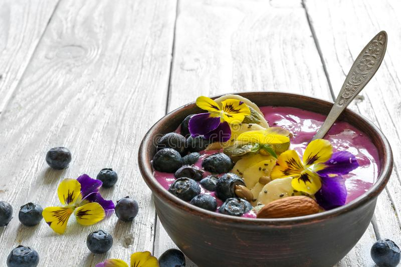 Smoothie bowl with a spoon topped with fresh berries, banana, chia seeds, nuts and flowers for healthy breakfast stock images