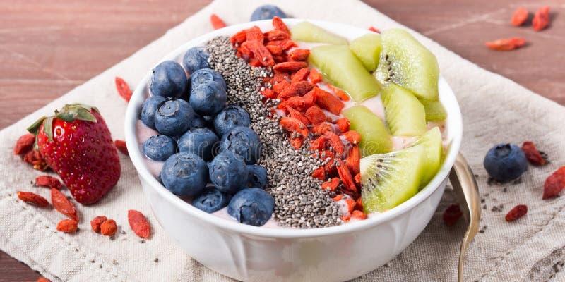 Smoothie bowl with strawberry smoothie, berries, kiwi and chia royalty free stock photo