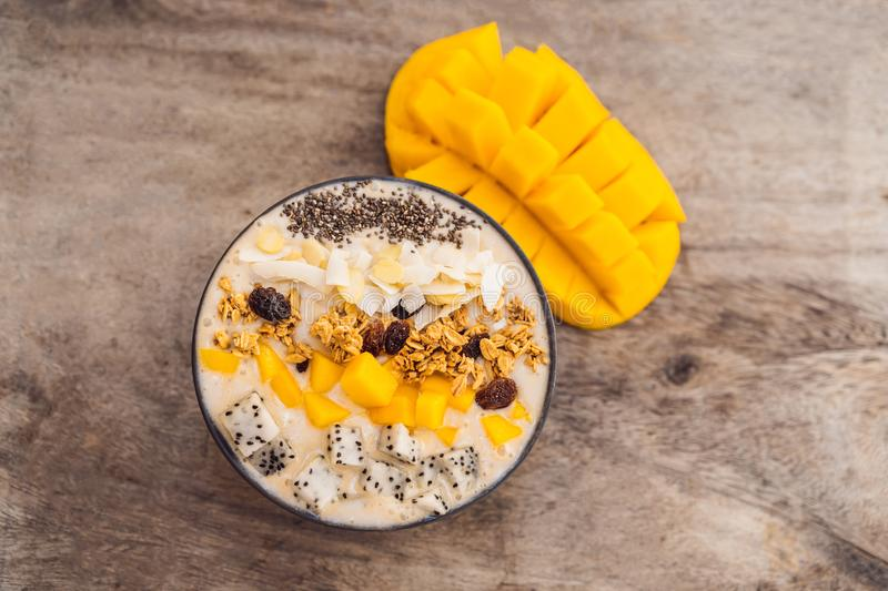Smoothie bowls made with mango, banana, granola, grated coconut, dragon fruit, chia seeds and mint on wooden background. Concept fruits, vitamins stock images