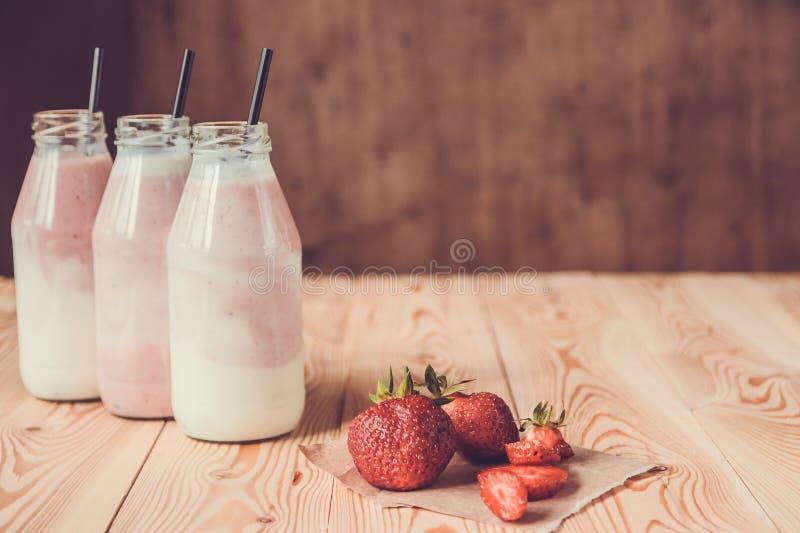 Smoothie con la fresa en botellas en la tabla de madera imagenes de archivo