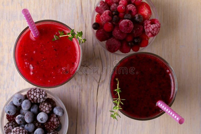 Smoothie congelado de las bayas del verano: arándanos, fresas, frambuesas, arándanos, pasas y zarzamoras en backgroun de madera imagenes de archivo