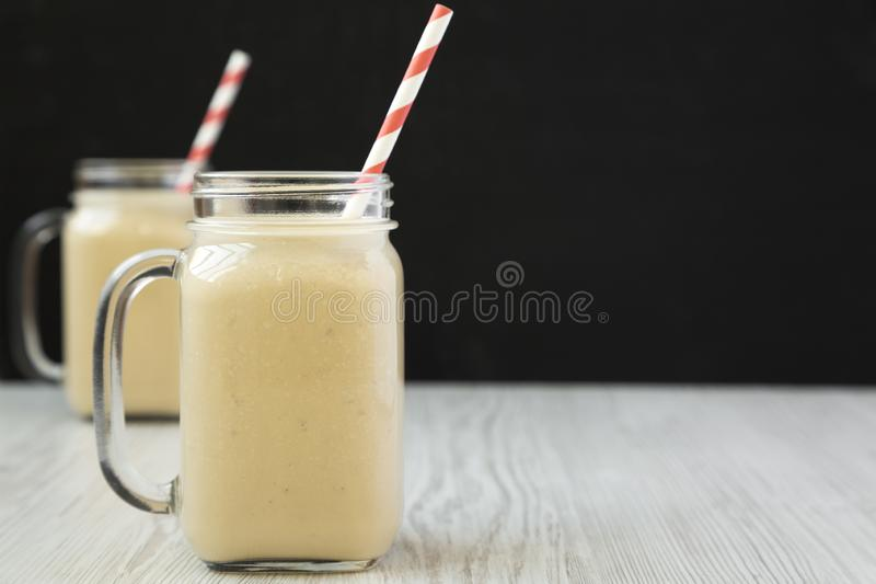 Smoothie de banane de beurre d'arachide dans des tasses en verre de pot, vue de côté Copiez l'espace photo stock