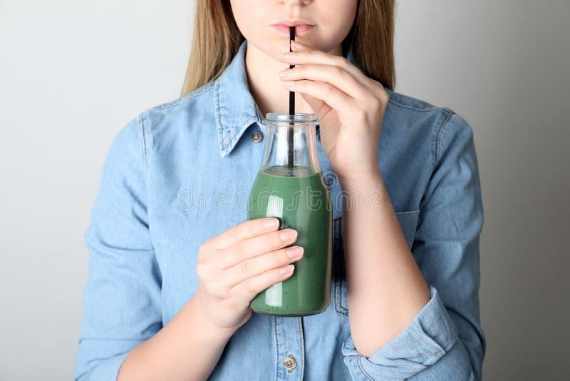 Smoothie de consumición del spirulina de la mujer de la botella en fondo gris imagen de archivo