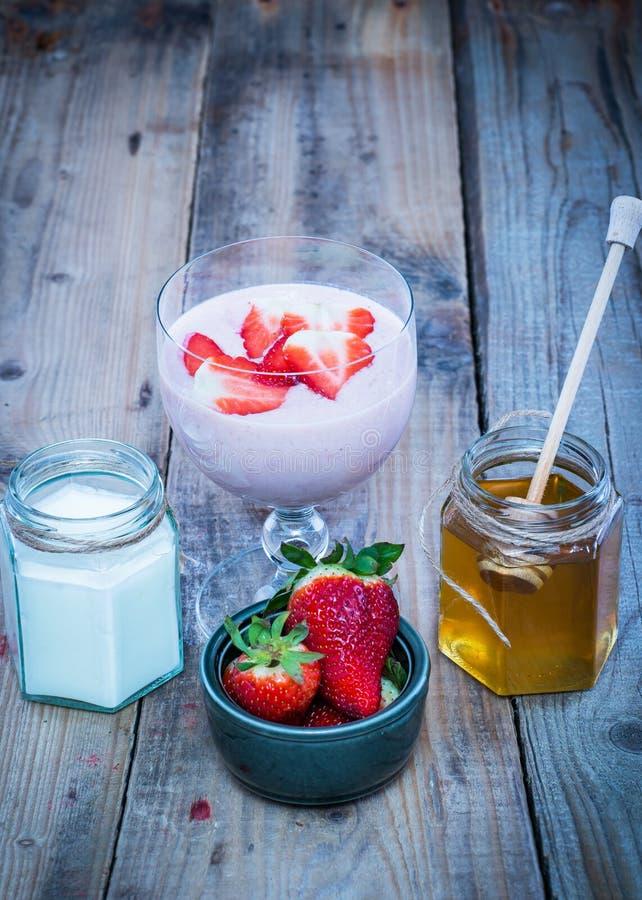 Smoothie de la fresa en un vidrio con los ingredientes a un lado foto de archivo