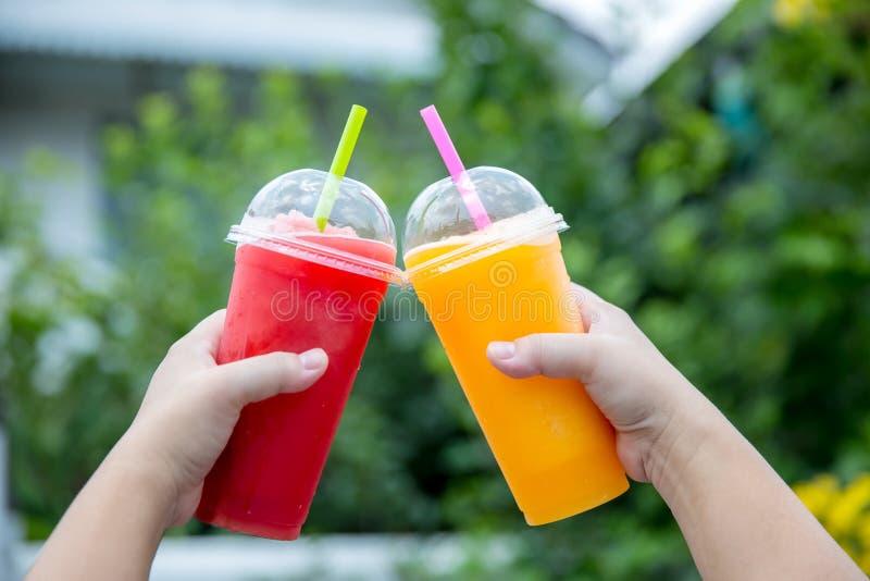 Smoothie de la fruta Mano que sostiene la taza pl?stica de smoothie colorido de la fruta en el caf? lindo Mano que sostiene la ta fotos de archivo libres de regalías