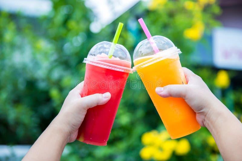Smoothie de la fruta Mano que sostiene la taza pl?stica de smoothie colorido de la fruta en el caf? lindo Mano que sostiene la ta imagen de archivo libre de regalías