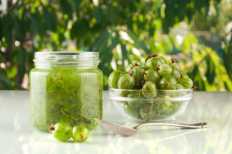 Smoothie de la grosella espinosa en un tarro en una tabla y un fondo marrones de hojas verdes fotografía de archivo libre de regalías