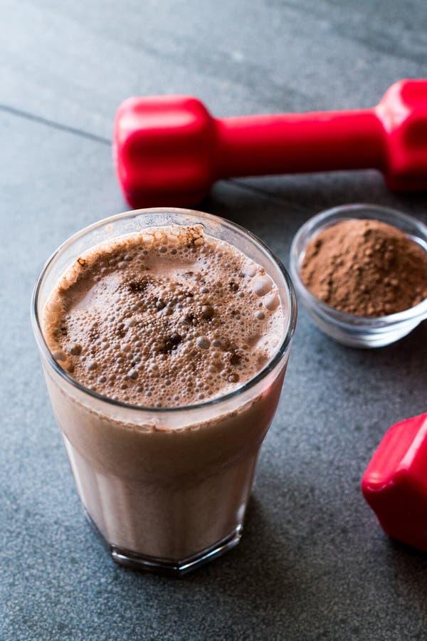 Smoothie de la sacudida de la proteína del chocolate con el polvo de la proteína y las pesas de gimnasia rojas foto de archivo