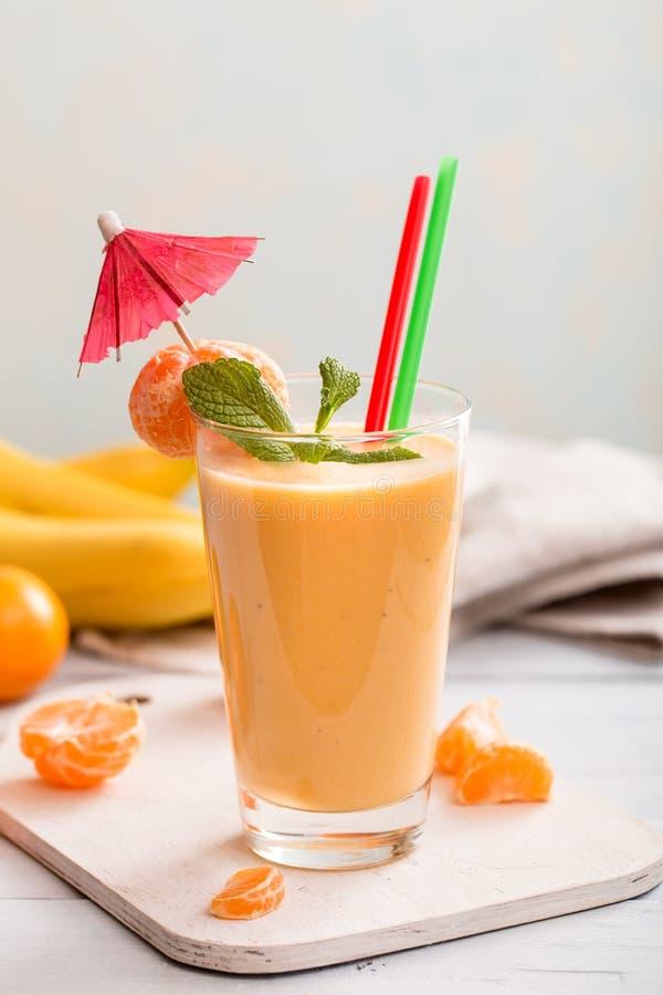 Smoothie de mandarine et de banane sur la table photographie stock libre de droits