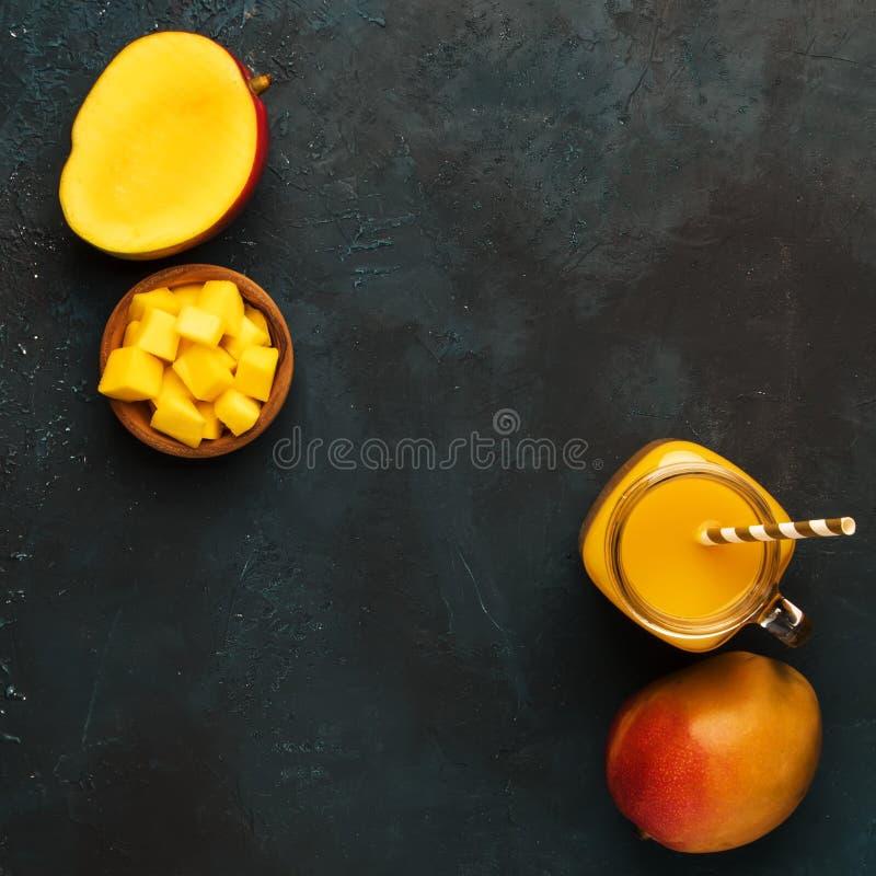 Smoothie de mangue dans le pot en verre avec le fruit frais sur le fond bleu, l'espace de copie, vue supérieure photo libre de droits