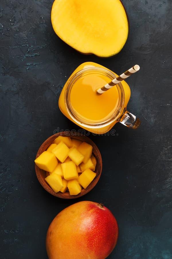Smoothie de mangue dans le pot en verre avec le fruit frais sur le fond bleu, l'espace de copie, vue sup?rieure photos stock