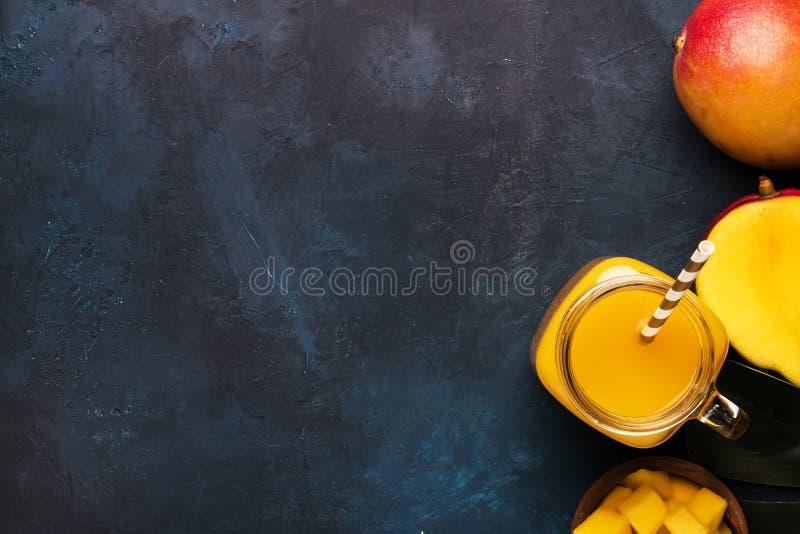 Smoothie de mangue dans le pot en verre avec le fruit frais sur le fond bleu, l'espace de copie, vue sup?rieure photo libre de droits