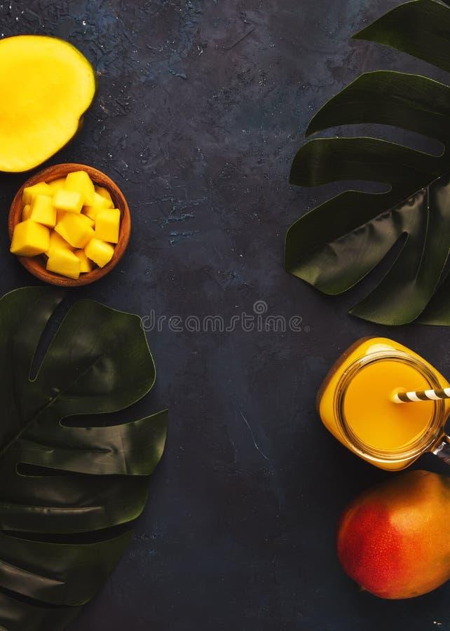Smoothie de mangue dans le pot en verre avec le fruit frais sur le fond bleu, l'espace de copie, vue sup?rieure photographie stock libre de droits