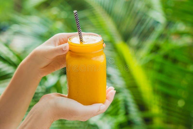 Smoothie de mangue dans un pot et une mangue de maçon en verre sur un fond vert Secousse de mangue Concept de fruit tropical photo libre de droits