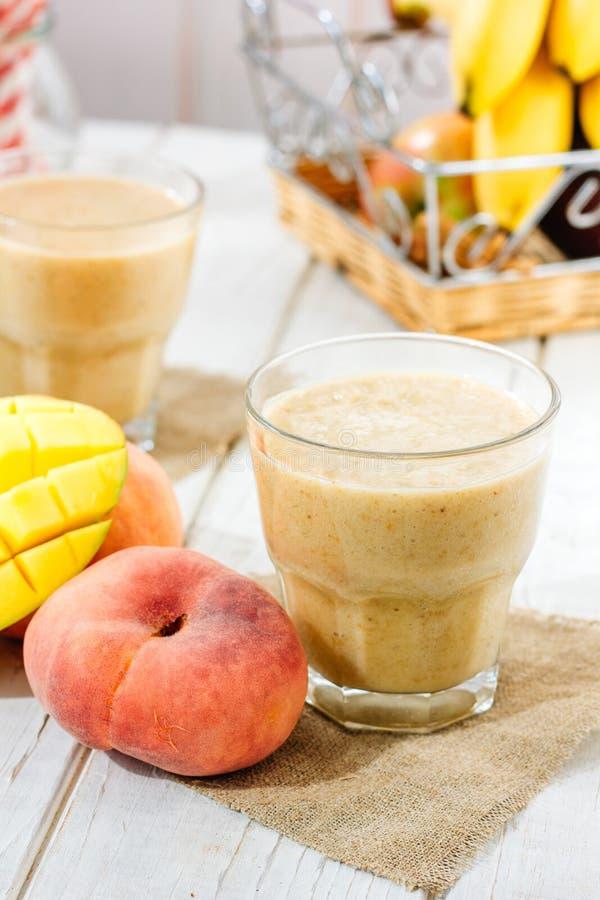 Smoothie de mangue et de pêche sur la table en bois avec des ingrédients photographie stock libre de droits