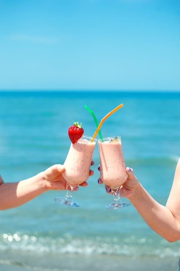 Smoothie del zumo de fruta dos en tazas de cristal clásicas de bayas en fondo de la agua de mar de los turquois del verano Dos al foto de archivo