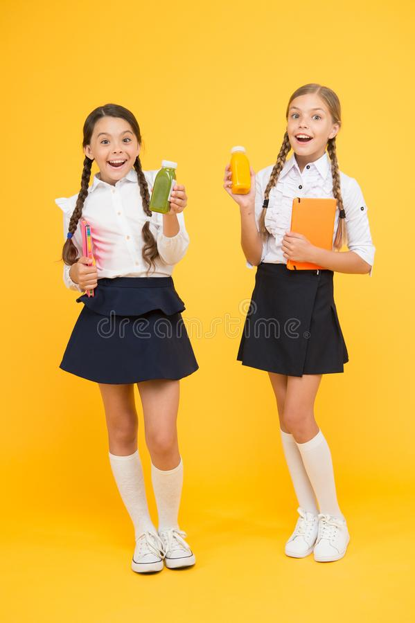 Smoothie detox. Yummy smoothie. Healthy nutrition. Schoolgirls holding juice bottle on yellow background. Quenching. Thirst during school time. Thirst and royalty free stock photography