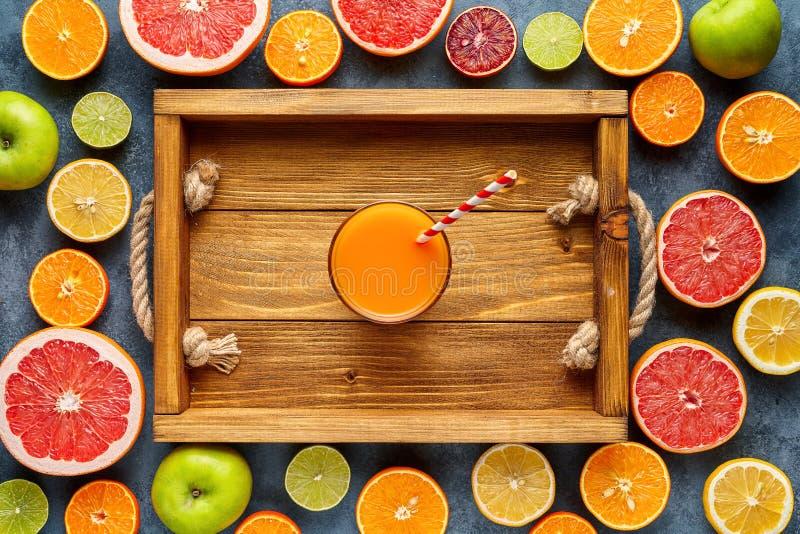Smoothie eller ny fruktsaft i trämagasin i den lekmanna- citrusfruktbakgrundslägenheten, organisk antioxidant för sund livsstilst royaltyfri bild