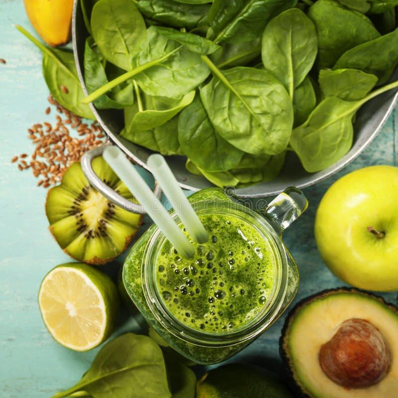 Smoothie et ingrédients verts sains sur le fond bleu photo stock