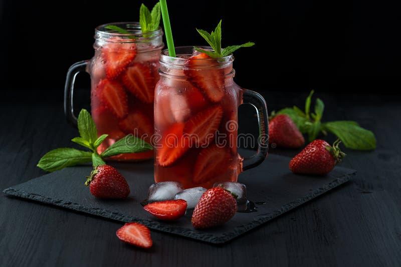 Smoothie fresco da morango Cocktail fresco do ver?o com morangos e cubos de gelo em um fundo escuro em uma tabela de madeira pret fotografia de stock