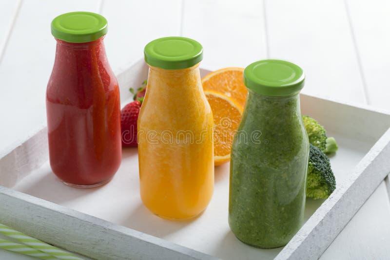 Smoothie fresco de la fresa, de la naranja y del bróculi en tres botellas con las frutas y verduras en un fondo rústico de madera fotografía de archivo