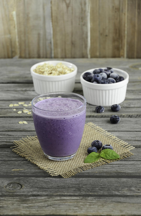 Smoothie with frozen blueberry and oatmeal on the wooden table royalty free stock photo