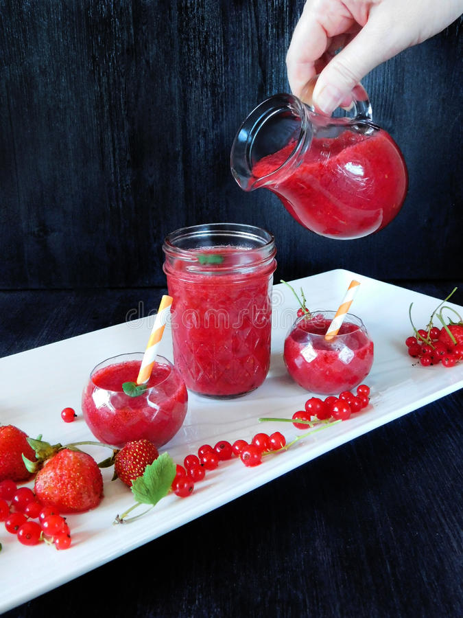 Smoothie made of red berries is being poured with glass jug stock images