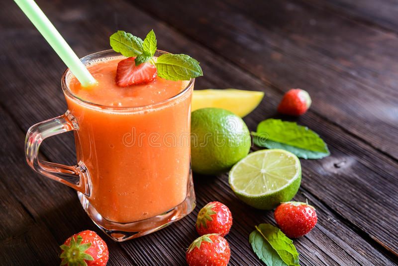 Smoothie med mango, jordgubbar och limefrukt royaltyfria bilder