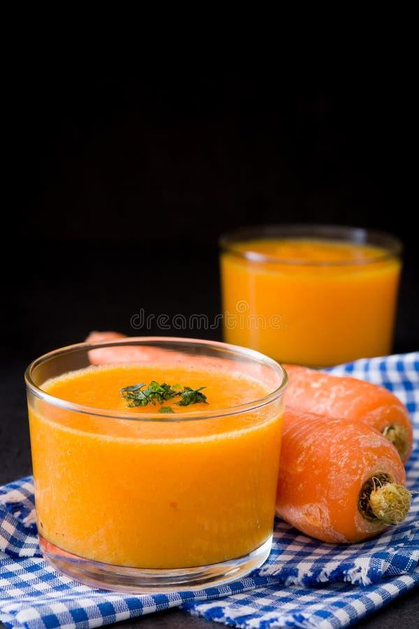 Smoothie med morötter på svart bakgrund arkivfoton