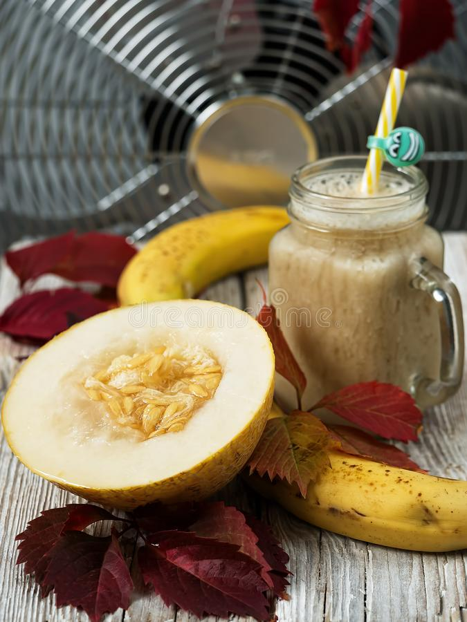 Smoothie with melon and banana. Juicy half melon on a wooden table next to bananas. Decorated with autumn leaves. Melon variety. With pulp of white-yellow color royalty free stock images
