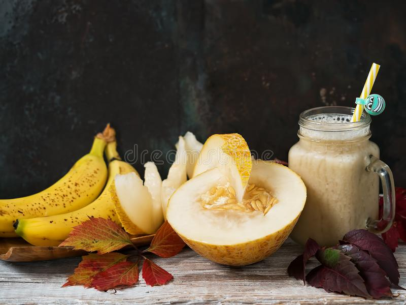 Smoothie with melon and banana. Juicy slices of ripe melon on a wooden plate next to bananas. Decorated with autumn leaves. Melon. Variety with pulp of white stock photos