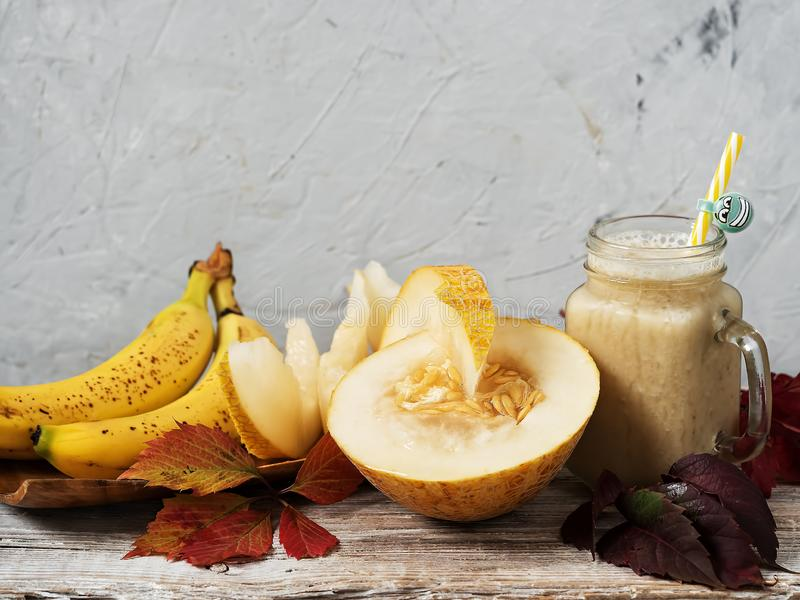 Smoothie with melon and banana. Juicy slices of ripe melon on a wooden plate next to bananas. Decorated with autumn leaves. Melon. Variety with pulp of white royalty free stock images