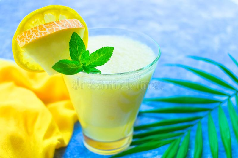 Smoothie from melon with mint in a glass on a blue background. Close-up. Concepts of summer soft drinks. royalty free stock image