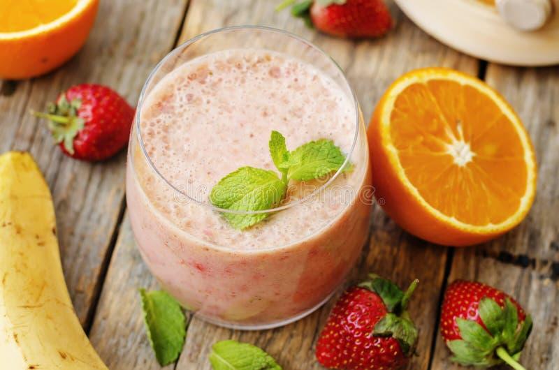 Smoothie met aardbeien, banaan en sinaasappel stock afbeeldingen