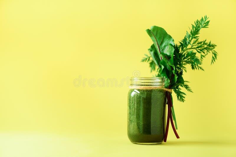 Smoothie met bietengreens en wortelbovenkanten op gele achtergrond, exemplaarruimte Het voedselconcept van de de zomerveganist Ge royalty-vrije stock afbeeldingen