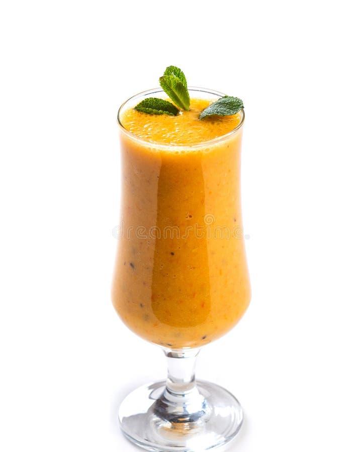 Smoothie orange dans un verre d?cor? d'une feuille de menthe sur un fond blanc d'isolement images stock