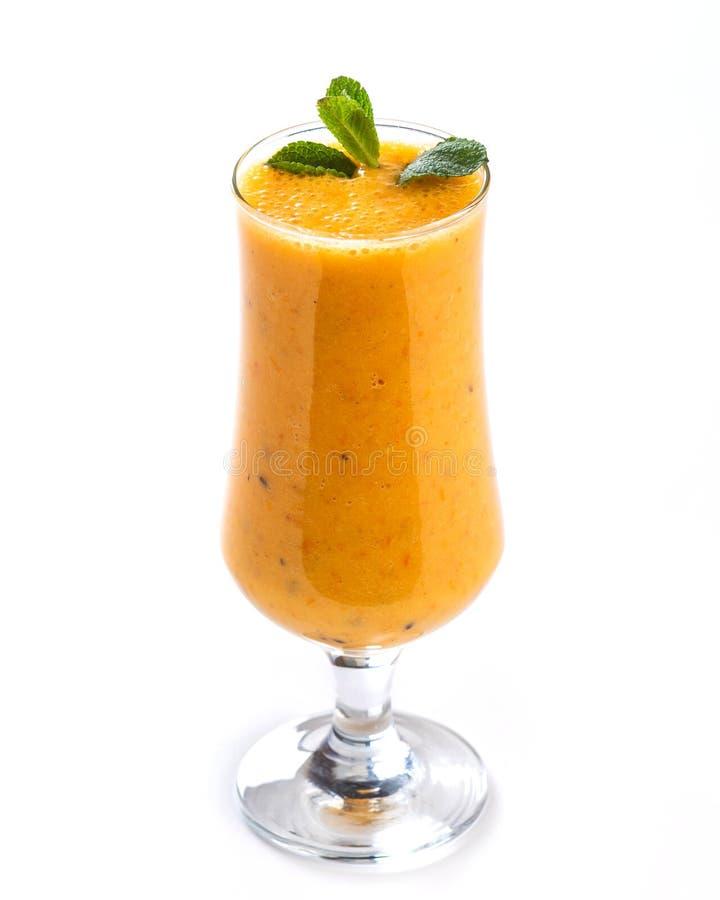 Smoothie orange dans un verre grand décoré d'une feuille de menthe sur le fond blanc d'isolement photo libre de droits