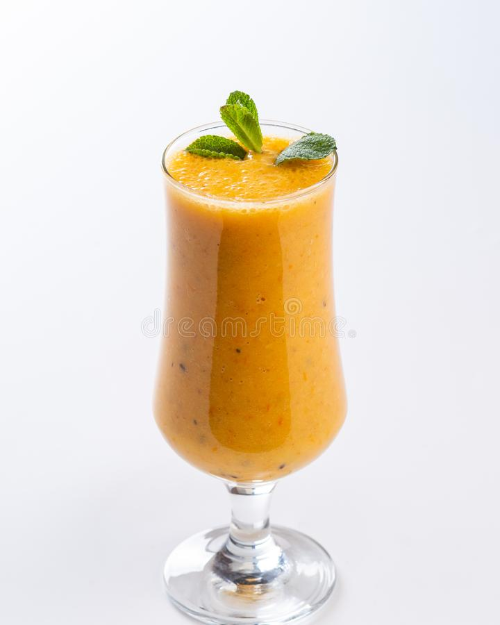 Smoothie orange dans un verre grand d?cor? d'une feuille de menthe sur le fond blanc photos stock