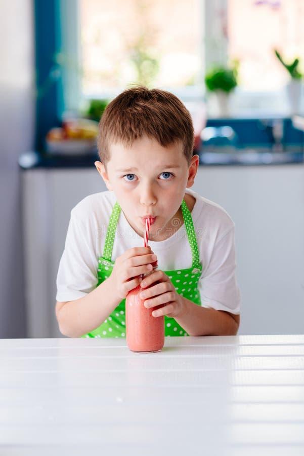 Smoothie potable de fraise de garçon d'enfant photographie stock